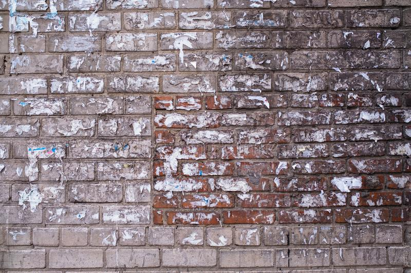 Old brick wall of the house with the torn-off ads. Texture. royalty free stock images